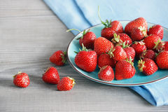 Ceramic plate with strawberries at old wooden table Stock Photos