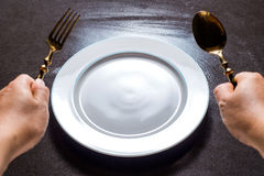 Ceramic plate on the table with spoon and fork in hand waiting f Royalty Free Stock Photos