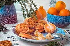 Ceramic plate with Viennese waffles, mandarins, spruce branches on white background stock image
