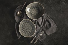 Ceramic plates and silverware. Top view of ceramic plates and rustic silverware on linen on black surface royalty free stock images