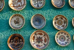Ceramic plates and souvenirs. Romanian pottery on green wall Royalty Free Stock Photos