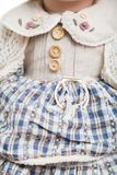 Ceramic porcelain doll in knitted old plaid dress Stock Photo