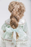 Ceramic porcelain handmade blond doll in dress with long pigtail. Back view of ceramic porcelain handmade vintage doll with long blond hair and elegant pigtail Stock Photography