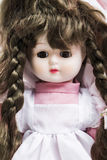 Ceramic porcelain handmade brunette doll with pigtails in pink dress Stock Photos