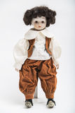 Ceramic porcelain handmade doll of a brunette boy in brown costume. Portrait of ceramic porcelain handmade vintage doll of brunette boy with curly hair in in old royalty free stock image