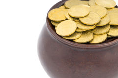 Ceramic pot with metal money. Ceramic pot with metallic money of the yellow metal on a white background Stock Photo