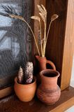 Ceramic pots on the windowsill. Three ceramic pots with spikelets, corn stand on the windowsill royalty free stock photo