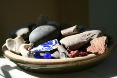 Ceramic pottery dish filled with china, marbles, rocks shells berries. Ceramic pottery dish filled with old primitive china, marbles, rocks, shells, and berries Royalty Free Stock Images