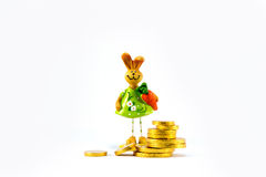 Ceramic rabbit and gold coins. Stock Photos
