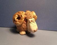 Ceramic ram. Handmade souvenir symbol of new 2015 year ram close-up on blue background Stock Photos
