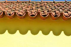 Ceramic tiles and shade on yellow house wall Stock Images