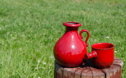 Ceramic red water jug and cup on stump on nature Stock Image