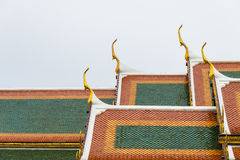 Ceramic roof tile temple in Thailand with cloudy sky Royalty Free Stock Images