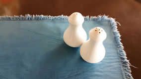 Ceramic of salt bottle and pepper bottle on blue plate cloth. On the wooden table Royalty Free Stock Images