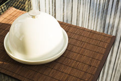 Ceramic salver with white dish over glass table Stock Image