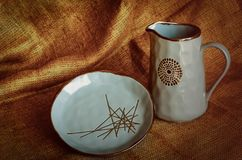 Ceramic set of dishes from a jug and a plate against the background of a piece of burlap. Pottery craft. Revival of folk tradition royalty free stock images
