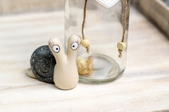 Ceramic snail looking at you. Beside a bottle Royalty Free Stock Image