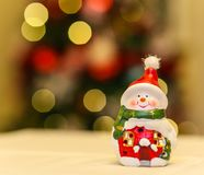 Ceramic snowman decoration with christmas tree lights. Ceramic snowman decoration with beautiful bokeh with christmas tree lights in the background Stock Images