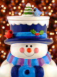 Ceramic snowman smiling and wearing winter clothing. Christmas lights in background Stock Image