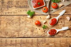 Ceramic spoons with tomato sauce and spices. On wooden table royalty free stock image