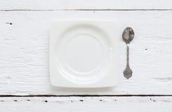 Ceramic square dessert plate and tea spoons Stock Photos