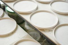 Ceramic studio, plane white plates ready to glaze and baking royalty free stock photography