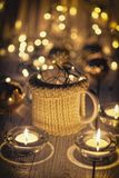 Ceramic stylish cups in sweaters and christmas retro garland on bokeh lights background. Shallow depth of field. Tinted photo Royalty Free Stock Images
