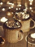 Ceramic stylish cups in sweaters and christmas retro garland on bokeh lights background. Shallow depth of field. Tinted photo Stock Images
