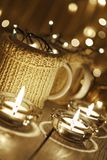 Ceramic stylish cups in sweaters and christmas retro garland on bokeh lights background. Shallow depth of field. Tinted photo Royalty Free Stock Image