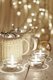 Ceramic stylish cups in sweaters and christmas retro garland on bokeh lights background. Shallow depth of field. Tinted photo Stock Image
