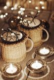 Ceramic stylish cups in sweaters and christmas retro garland on bokeh lights background. Shallow depth of field. Tinted photo Royalty Free Stock Photography