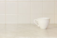 Ceramic tea cup on white kitchen table. Stock Photo