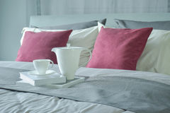 Ceramic tea set and books setting on bed with red velvet pillows at home Royalty Free Stock Photography