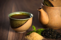 Ceramic teapot, cup of black tea with mint leaves and brown sugar on wooden table. Stock Photos
