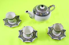 Ceramic teapot and cup on the green background stock photo
