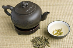 Ceramic teapot with green tea. Clay teapot with a cup full of green tea on a bamboo mat Stock Image