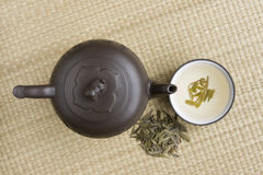 Ceramic teapot with green tea. Clay teapot with a cup full of green tea on a bamboo mat Royalty Free Stock Photos