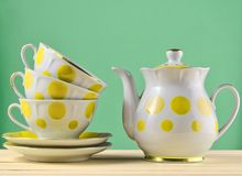 Ceramic teapot, a stack of cups in polka dots on a wooden table Stock Photos