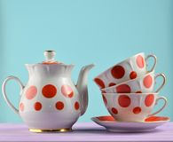 Ceramic teapot, a stack of cups in polka dots on a wooden table isolated on a blue pastel background. Copy space. Ceramic teapot, a stack of cups in polka dots royalty free stock photography