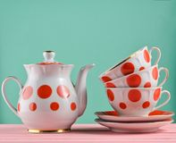 Ceramic teapot, a stack of cups in polka dots on a wooden table isolated on a blue pastel background. Copy space. Ceramic teapot, a stack of cups in polka dots stock photography