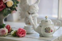 Ceramic teapot, сup, roses Stock Photos
