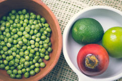 Ceramic terracota bowl with raw green peas next to. White plate of fresh organic tree tomato and limes Royalty Free Stock Image