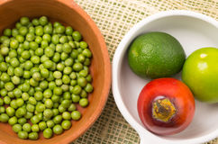 Ceramic terracota bowl with raw green peas next to Stock Photography