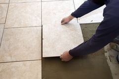Ceramic Tile. A man on his knees installing a ceramic tile floor Royalty Free Stock Image