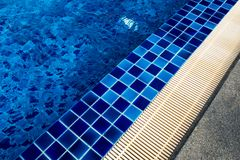 Ceramic tile flooring and drainage gutters beside the pool. Blue Ceramic tile flooring and drainage gutters beside the pool Royalty Free Stock Image