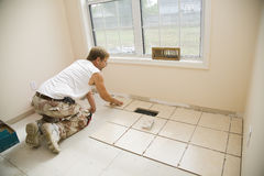 Ceramic tile installer. Man installing ceramic tile in customers kitchen, getting ready to sell home Royalty Free Stock Photo