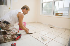 Ceramic tile installer. Man installing ceramic tile in customers kitchen, getting ready to sell home Royalty Free Stock Image
