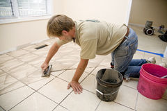 Ceramic tile installer. Installer filling ceramic tile with grout, home is being updating for resale on housing market Stock Images