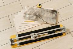 Ceramic tile, manual cutter, measuring tape and pencil Stock Photos