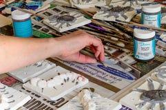 Ceramic tiles during the glazing process. WREXHAM, UNITED KINGDOM - MARCH 14, 2016: Ceramic 'mini beasts' tiles during the glazing process. Part of a workshop Stock Image